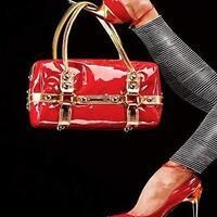 Photo of a women's foot holding up a red purse.