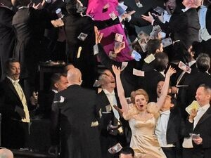 woman wearing gold ball dress singing while surrounded by male singers