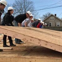 students lifting a wall