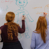 students writing on a board