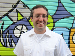 professor matthew rarey in white shirt standing in front of a mural.