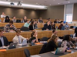 large lecture hall with students seated throughout.