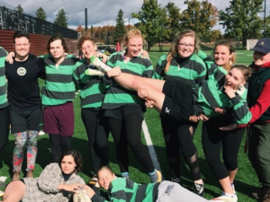 Members of Oberlin's Women & Trans' Rugby Team, the Rhinos, posing in their green and black striped jerseys after a match on Bailey field.