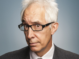 Robert Post with disheveled white hair wearing black rectangular glasses along with a dark suit and tie.