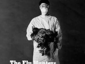 man wearing hospital scrubs with face mask holding a large bird.