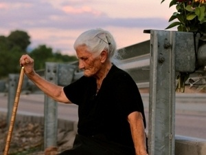 Silence of Others features old white haired woman sitting on a bench holding a wooden cane.