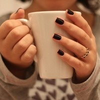 Hands with dark-painted fingernails holding white mug