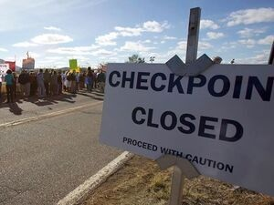 desert area with a big sign saying checkpoint closed.