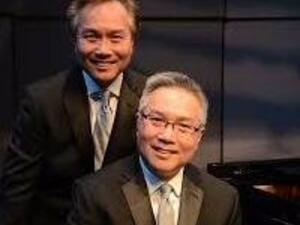 two Asian men in suits sitting near a piano.