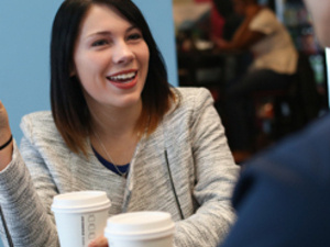 Female student smiling and holding a cup of coffee as she talks with a male student