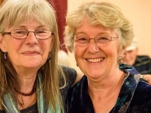 two older women with glasses standing close to one another and smiling.