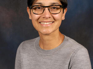 woman in crew neck grey sweater with short dark harad and  glasses.