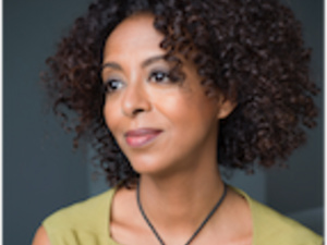 black woman with thick wavy hair and light green top looking away from camera