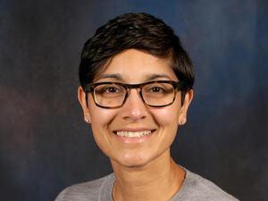 woman with dark hair and dark glasses and gray crewneck shirt facing straight ahead.