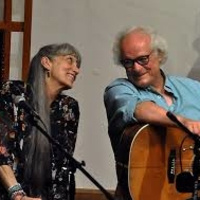 woman with long gray hair sitting next to man with gray hair and glasses and holding a guitar.