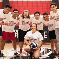 Students of the intramural volleyball league pose in front of a net
