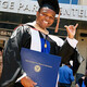 A man in commencement regalia gives UTA Maverick handsign while holding a diploma