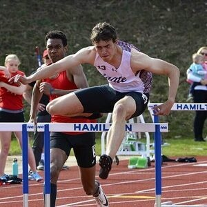 Warren Carter leaps over a hurdle during a race