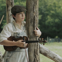 "Photo of a boy holding a violin from the movie ""The Mountain Minor""."