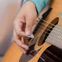 photo of an individual playing a guitar.