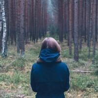 Woman standing in forest. Credit: @jordaneil, Unsplash