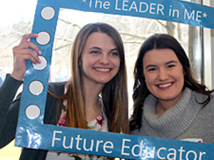 "two education majors at the 2018 event holding a photo frame that says ""The Leader in me"" Future Educator"