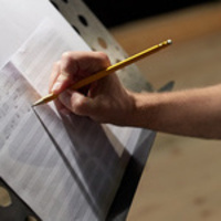 Closeup of person's hand with pencil composing music on paper on a music stand.
