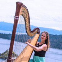 Harp player posing with harp with Lake Tahoe as a backdrop