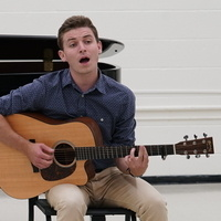 A student plays a guitar.
