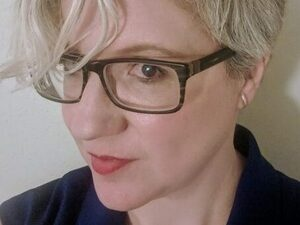 Margaret Schedel with short blond hair wearing glasses