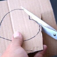 hands cutting out a cardboard heart