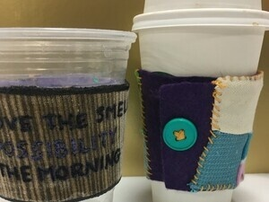 photo of two coffee cups with coffee coats