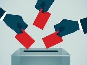 hands dropping ballots into ballot box