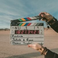 Two hands holding a clapperboard against a desert background