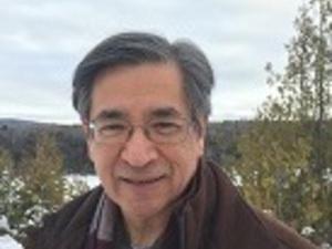 Portrait of Bernard C. Perley dressed in brown overcoat, plaid scarf, blue shirt standing outdoors