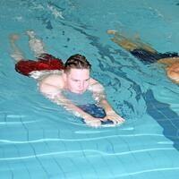 man swimming with kick board