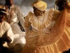 African American woman in flowing yellow dress dancing.