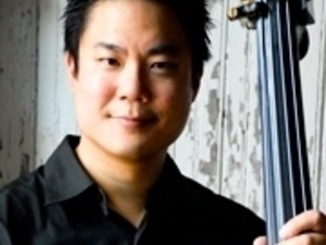 Owen Lee wearing black shirt, smiling, and holding double bass