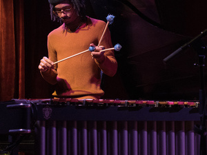 Vibraphonist Joel Ross stands behind the instrument holding three mallets.