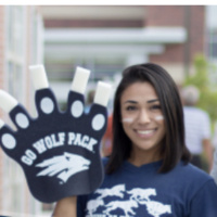 """Young woman smiling while wearing a foam """"go wolf pack"""" hand"""