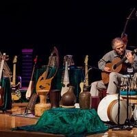 Todd Green on stage with many of his world music instruments.