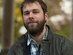 bearded man in heavy jacket and plaid shirt sitting outdoors for portrait.