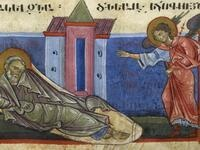 A medieval manuscript image. A saint is waking up from a dream while an angel points to him, presumably explaining the meaning behind it.