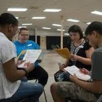Four Students sitting in a circle, each reading a piece of paper.