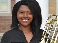 Image of Erica Nichols holding bass trombone