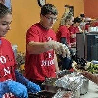Students serving food at a local services org