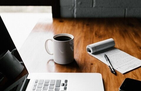 A picture of a laptop sitting beside a notepad, coffee, a pen and a cellphone.