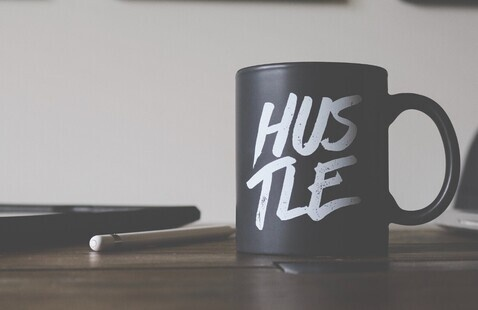 """A picture of a coffee mug with the word """"hustle"""" written on it."""