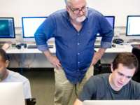 A professor stands behind two students working on desktop computers.