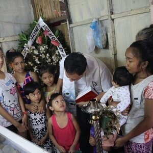 At the casket of a drug war victim...Fr. Pilario with the children, wife, and mother left behind